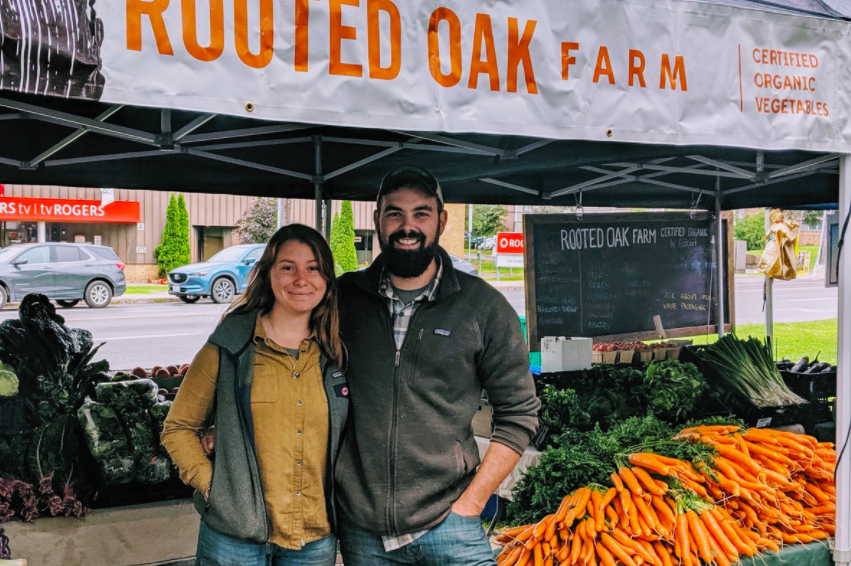 """A man and a woman stand together in front of a farmers' market stand with vegetables on display. Their tent has the words """"Rooted Oak Farm: Certified Organic Vegetables"""" written on it."""