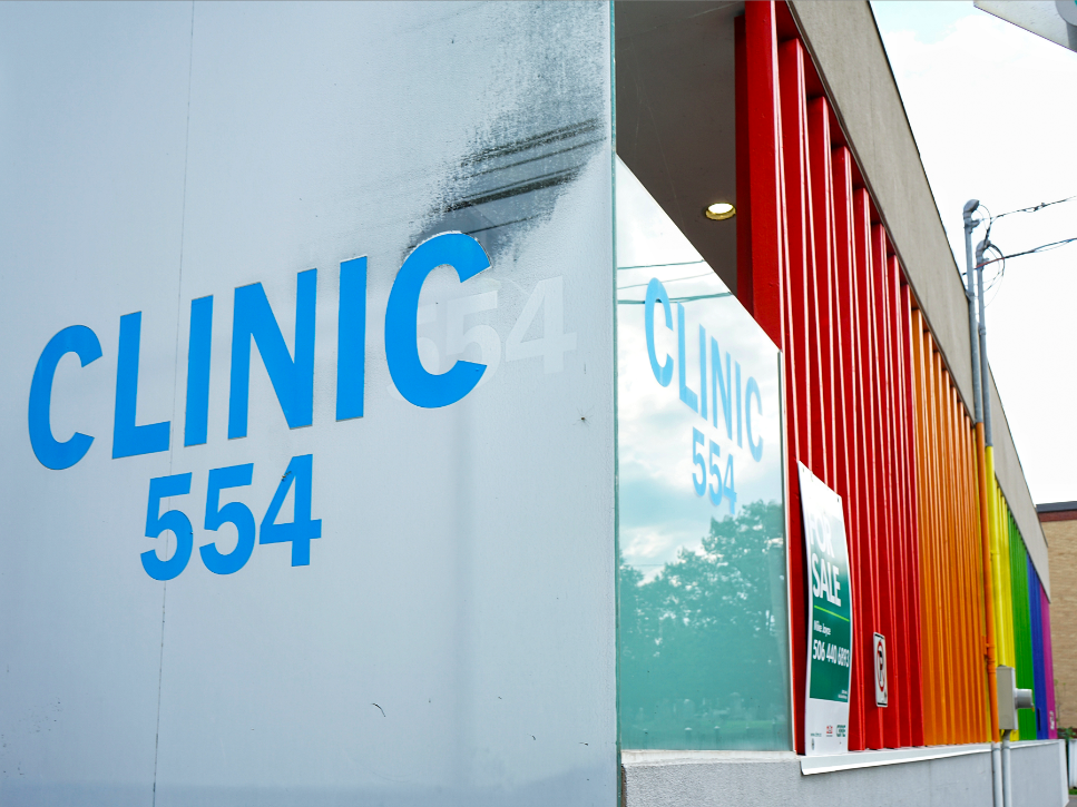 A photo of Clinic 554's exterior. The side of the building is painted in rainbow colours.