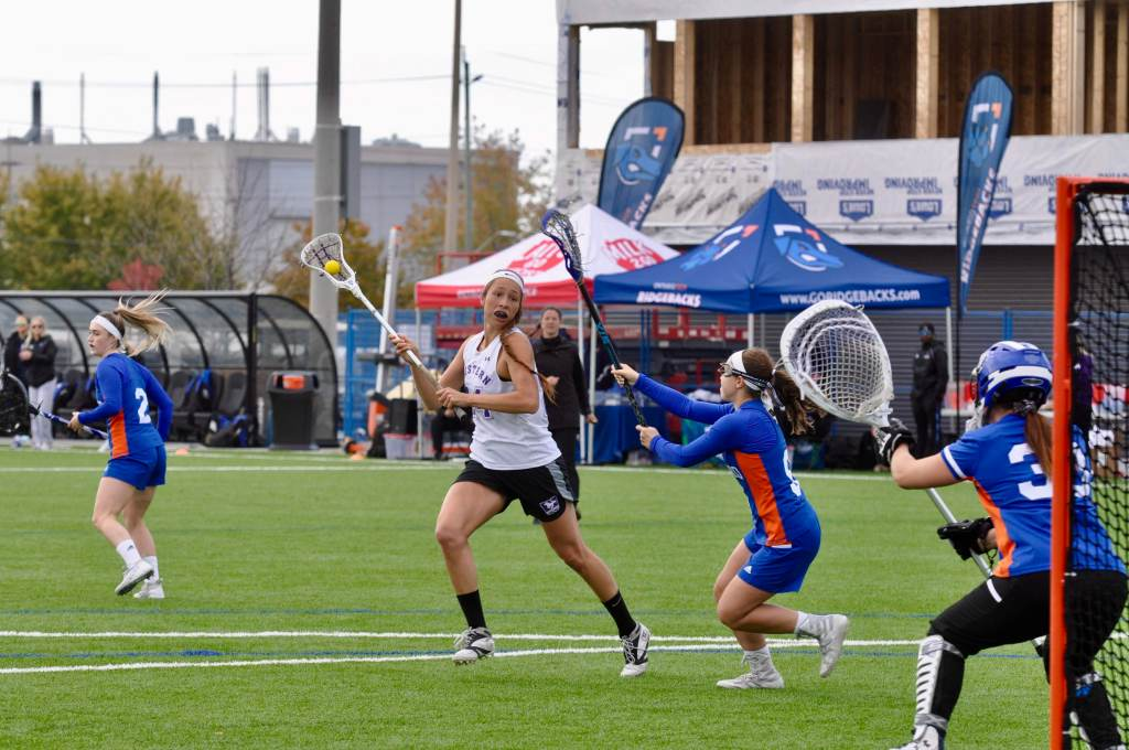 Fawn Porter playing lacrosse, about to throw a ball at the goal