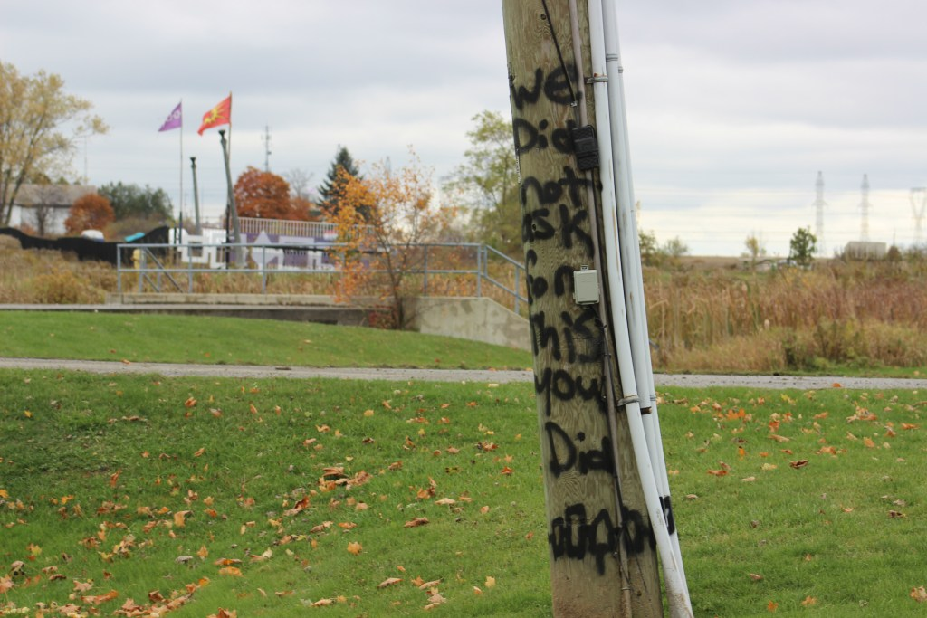 """A wooden post with """"We Did Not Ask For This You Did,"""" spray painted on it."""