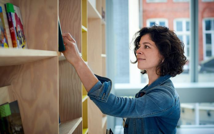 A woman browses books on a shelf. She is white with brown hair and is wearing a jean jacket
